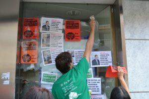 """Els activistes omplir d'enganxines el banc mentre cridaven:""""estas son nuestras armas"""" // Elisenda Colell"""