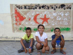 Els tres ifnats de l'intercanvi rere la bandera del seu país. // Molins de Rei amb el Sàhara
