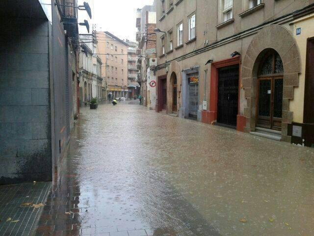 La Guàrdia Urbana ha hagut d'actuar en els embornals del carrer Rafael Casanova inundat // Jordi Costa