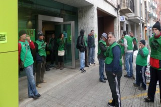 Els activistes davant de la sucursal amb xiulets i distinguits de color verd // Adrià Casaín