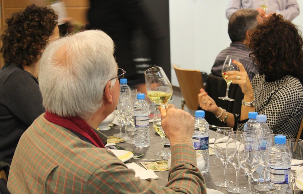 Un els assistents olorant un vi blanc maridat amb formatge // Jose Polo