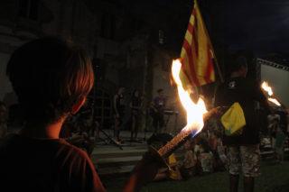 Un nen, amb la torxa a la mà, mira l'actuació de Komba't // Jose Polo