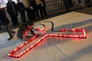 Una noia col·loca la seva espelma al gran llaç contra la violència masclista // Jose Polo
