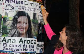 Ana Aroca, de Molins Camina, enganxa un cartell durant la campanya de les municipals // Jose Polo