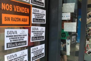 Detall de la porta del BBVA plena de pancartes // Jose Polo