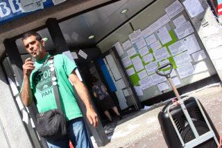 Un dels activistes de la PAH amb l'altaveu i la seu del BBVA empaperada // Jose Polo