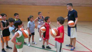 Un entrenador ensenya les bases del bàsquet a un grup de nens // CB Molins de Rei