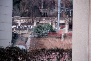 El pont destruït vist des de la carretera. Es poden veure les columnes que feien de porta d'accés abans i després de les vies del tren // Jordi Julià
