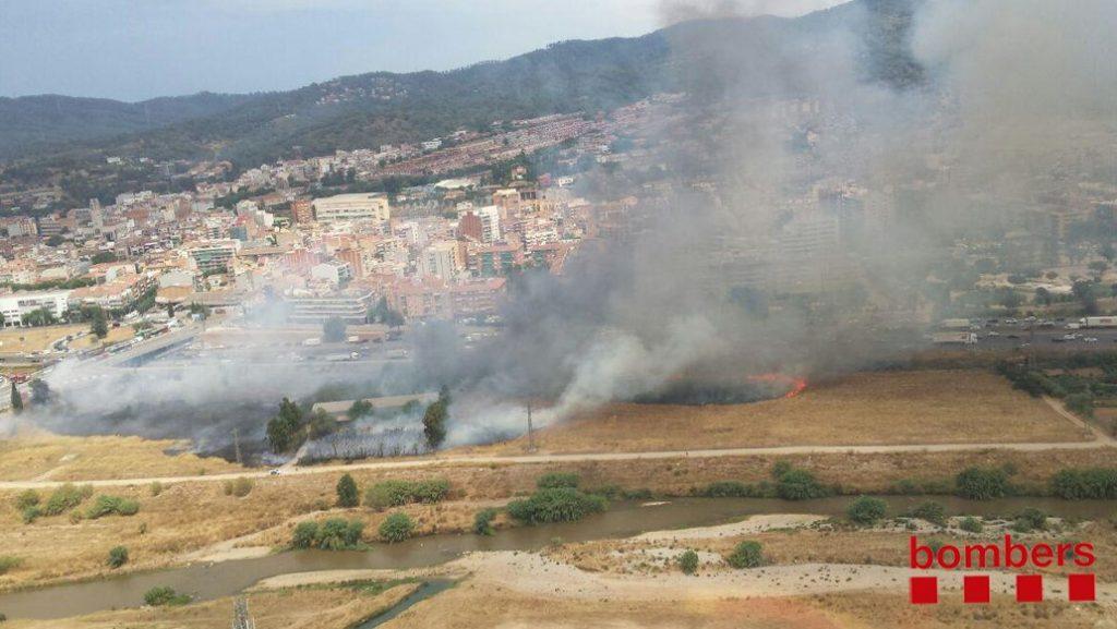Vista aèria de l'incendi, que ha provocat un intens fum davant de Molins de Rei // Bombers