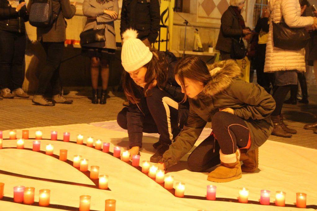 Dues noies col·locant espelmes en record de les dones assassinades // Roger Cuartielles